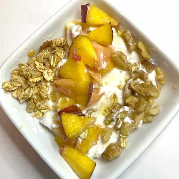 yogurt, granola, nuts, and nectarine on yogurt in bowl