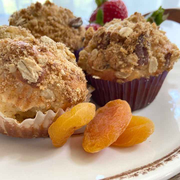 three apricot oat muffins on plate with fruit.