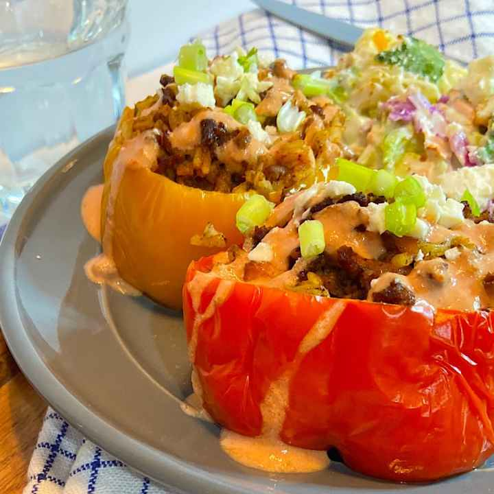 stuffed peppers on plate drizzled with yogurt sauce