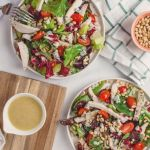 cup of tahini salad dressing with salads and pine nuts