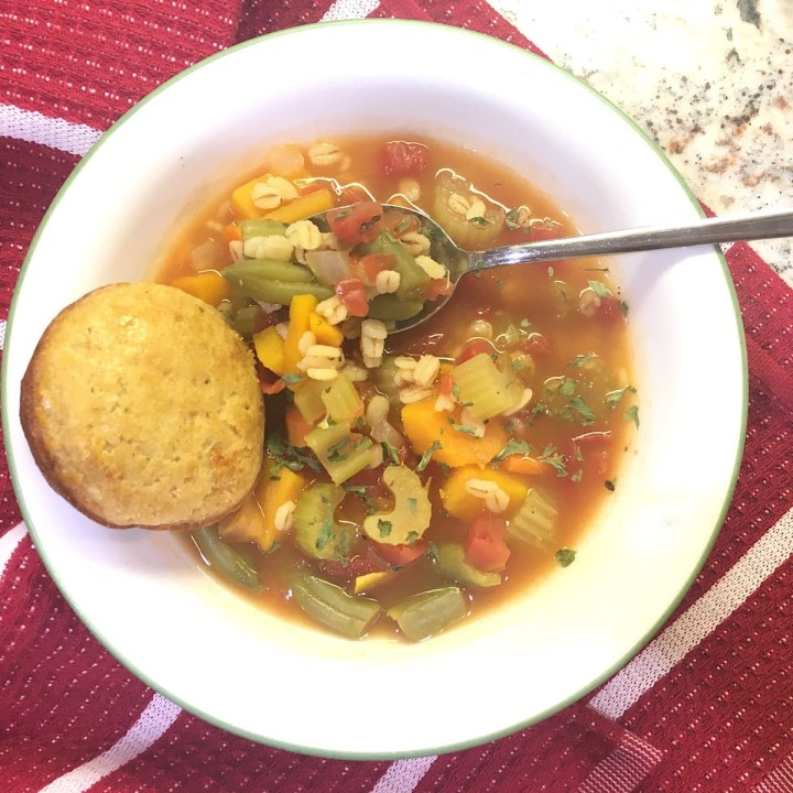 bowl of vegetable barley soup with muffin