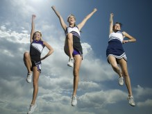 Three cheerleaders jumping