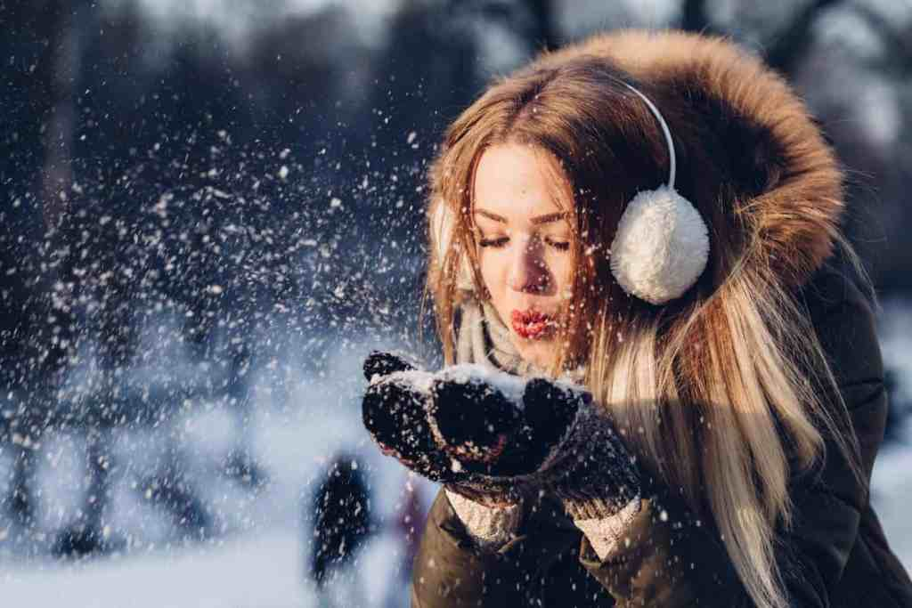 cozy girl in the snow - holiday wellness