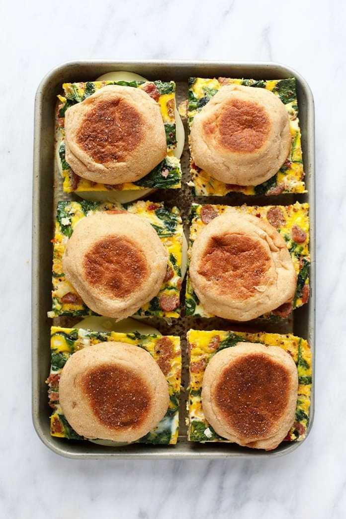 freezer breakfast sandwiches on a sheet pan ready to be wrapped and frozen