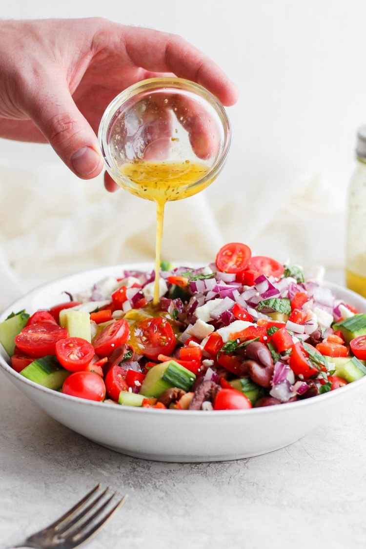 Pouring dressing onto the Greek Salad