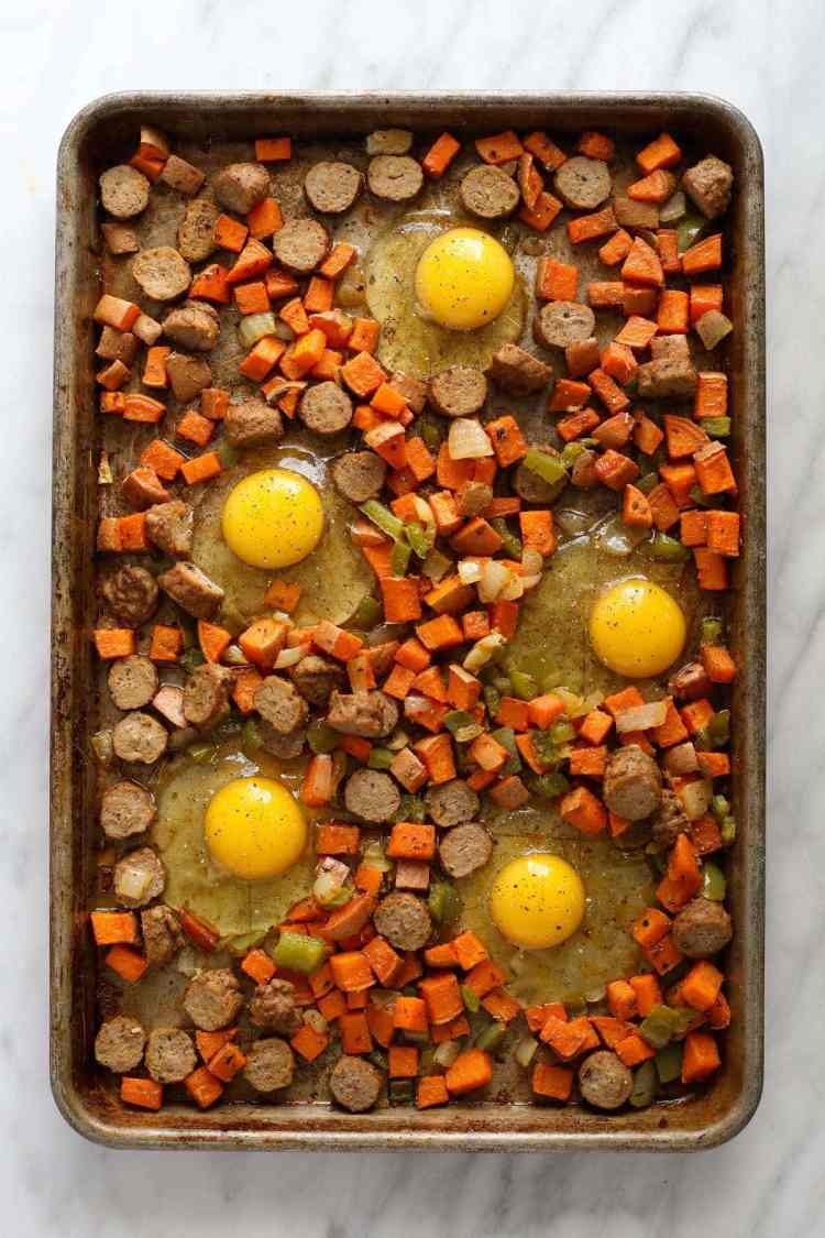 sweet potato nests with raw eggs cracked into them on sheet pan