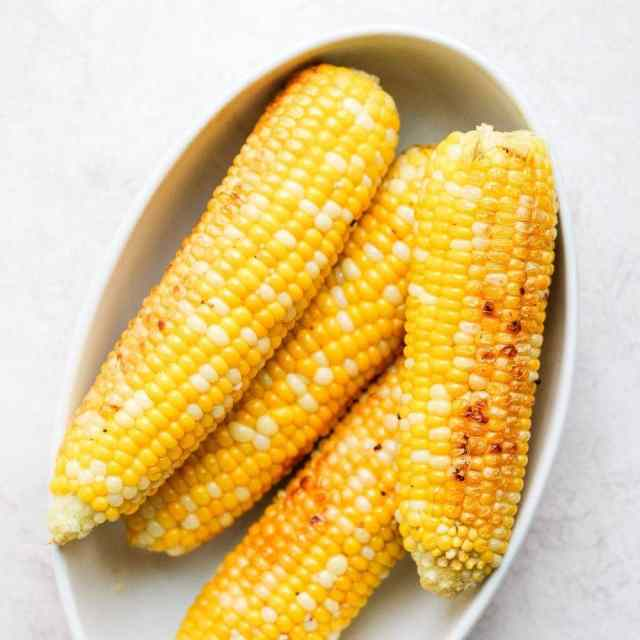 4 ears of corn in a bowl after being grilled