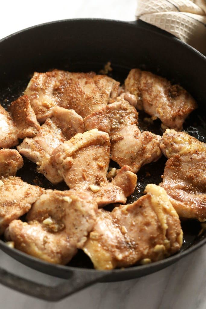 Boneless chicken thighs in a cast iron pan with dry rub