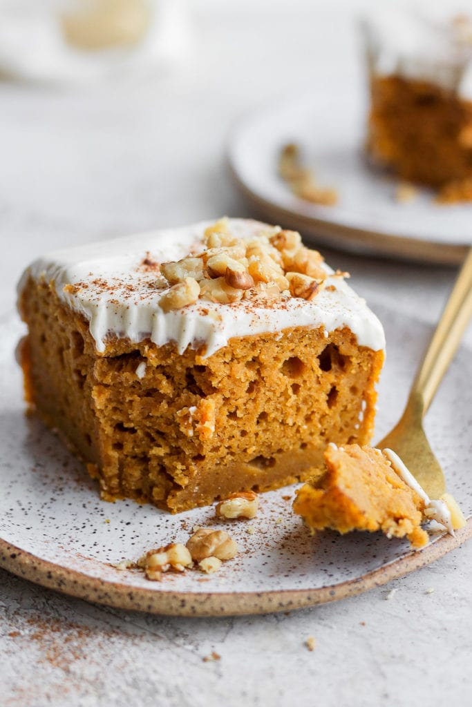 Piece of pumpkin sheet cake on a plate with a bite ready to eat on a fork