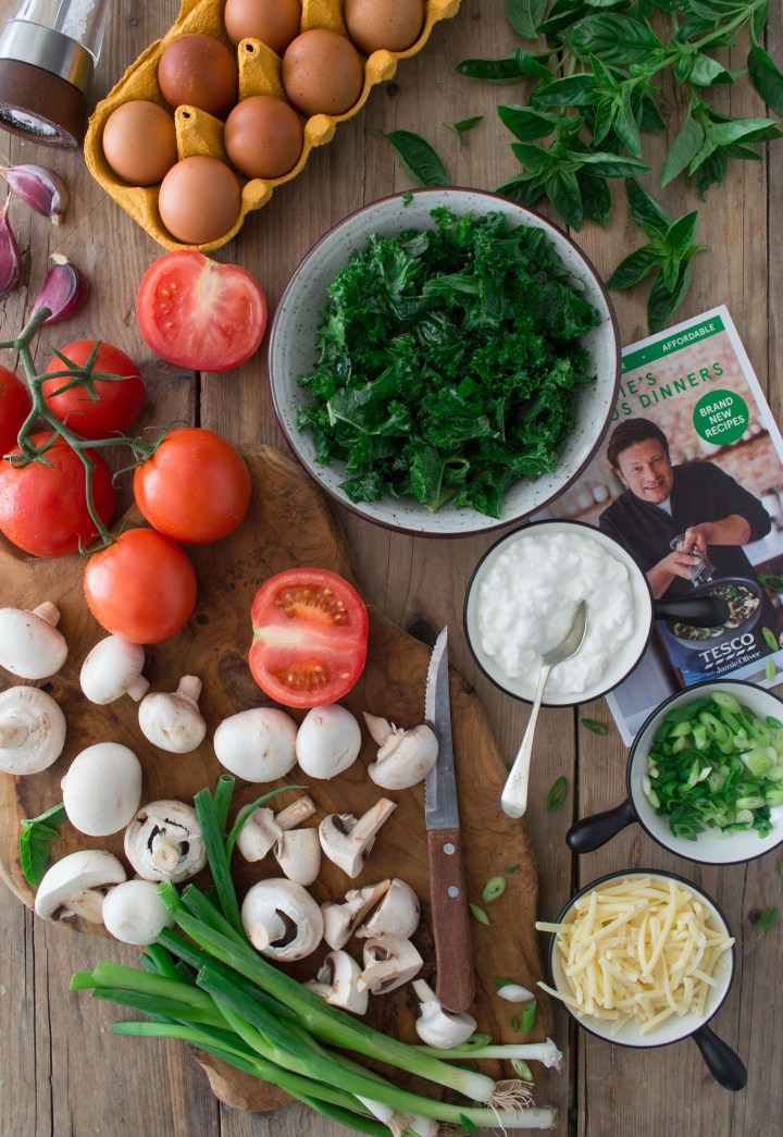 Mushrooms, tomatoes, kale, eggs, cottage cheese, spring onions, cheese on a wooden table
