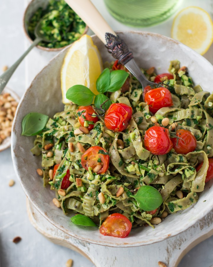 A bowl of pasta with cherry tomatoes, basil & lemon, fork inside the bowl