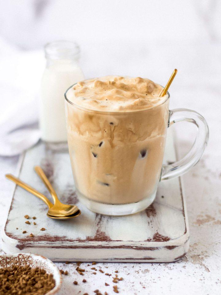Dalgona coffee on a white board on a glass mug, coffee granules on the side