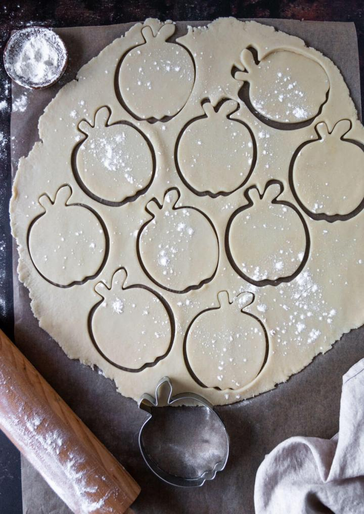 Top down view of pastry with cut out apple shapes & a rolling pin