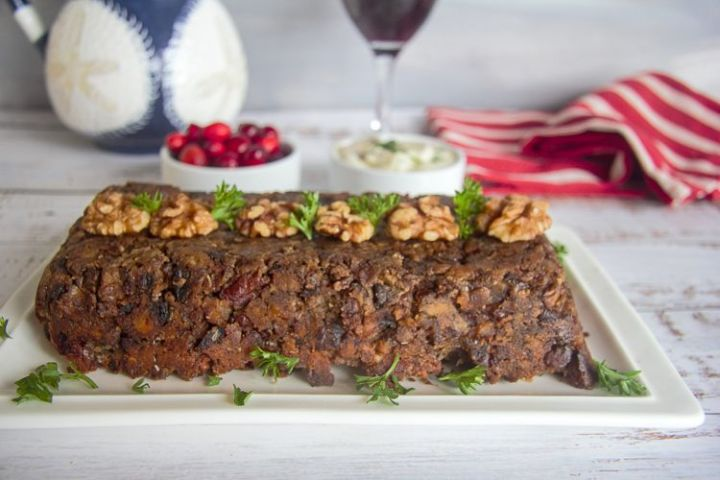 Close up of Keto Mushroom Walnut Loaf on a white table, cranberries and wine glass behind