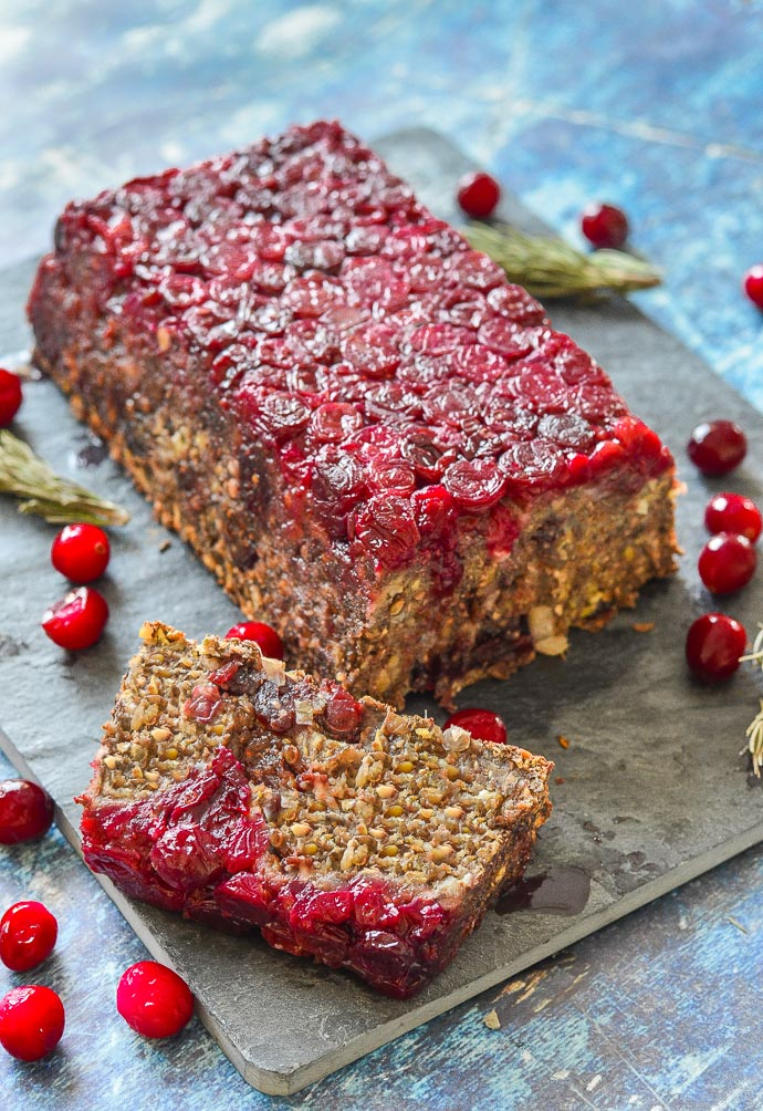 A close up of Mushroom Lentil Loaf with Cranberries , one slice cut, on a black slate board