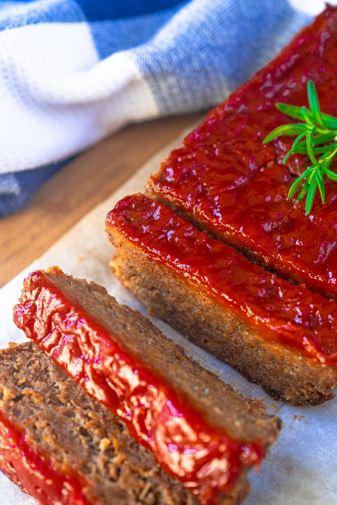 45 degree of vegan meatloaf topped with red ketchup glaze, 3 pieces cut