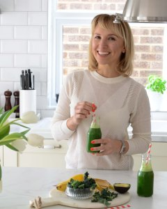 Tania in the white kitchen, holding a green smoothie