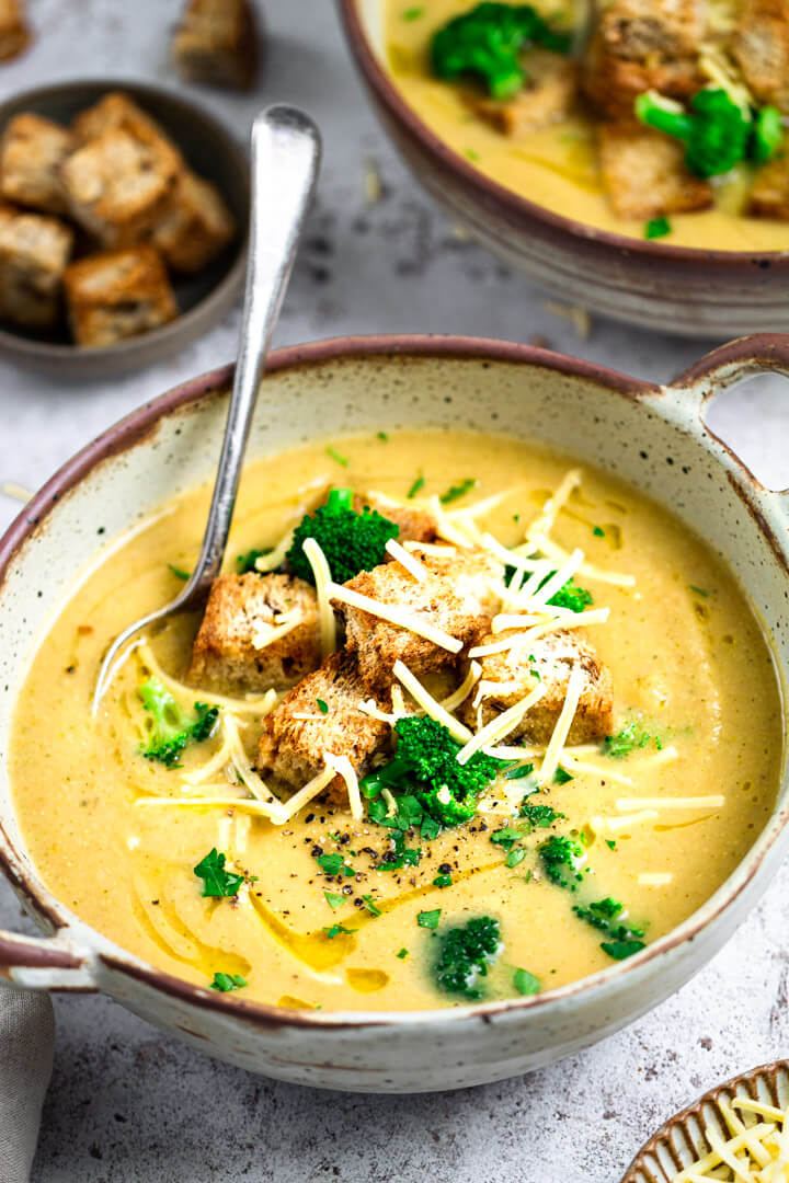 Head on view of vegan broccoli cheese soup in a round bowl with croutons