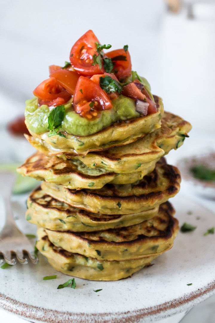 A stack of savoury vegan pancakes topped with guacamole and tomato salsa