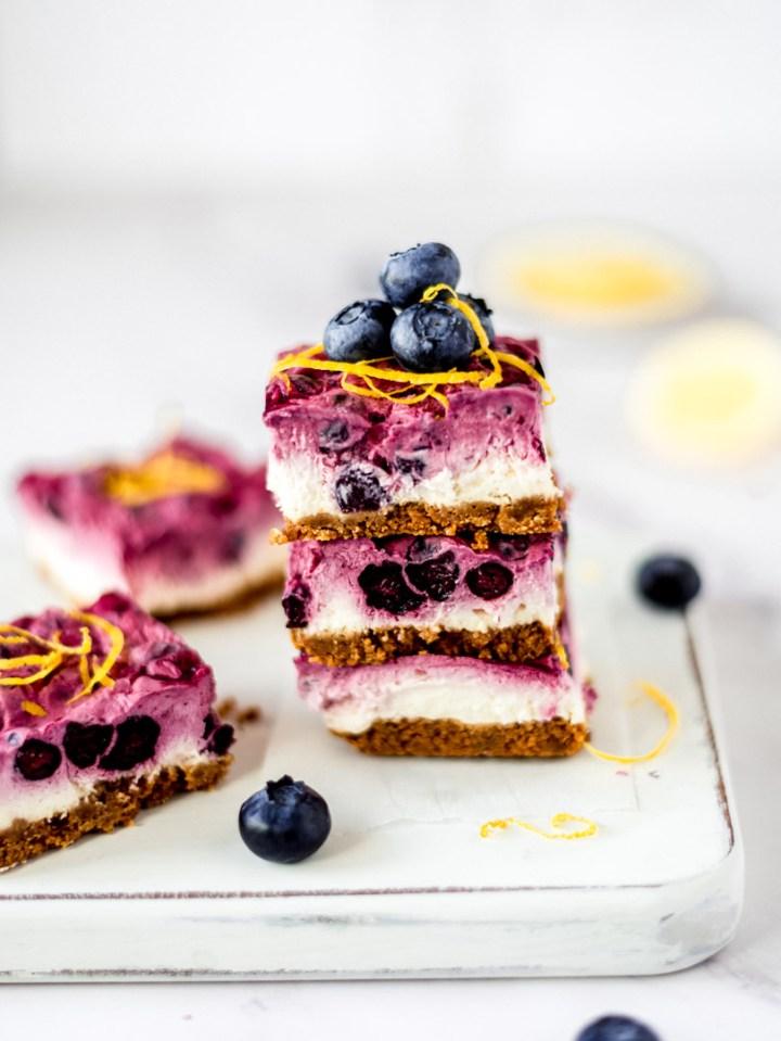 A stack of vegan blueberry lemon cheesecake bars
