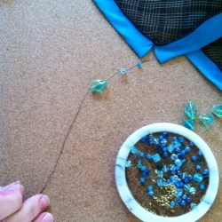 BEgin threading beaded accents through the needle to the thread.