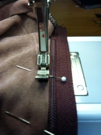 Stitch the zipper in place from the bottom to the top.