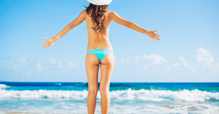 lady in swimsuit on beach with round buttocks