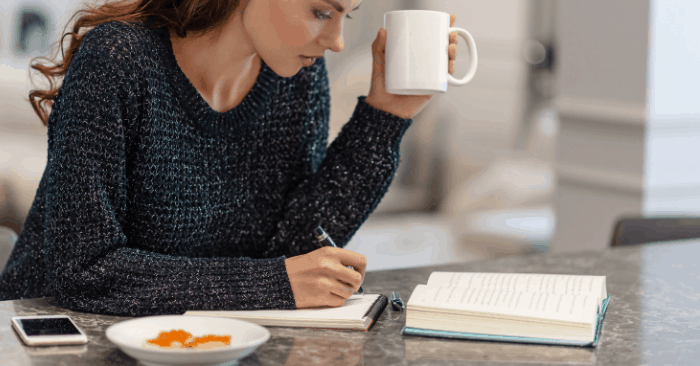 woman sitting at table writing down notes to start keto diet
