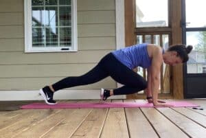 woman doing high plank to knee taps