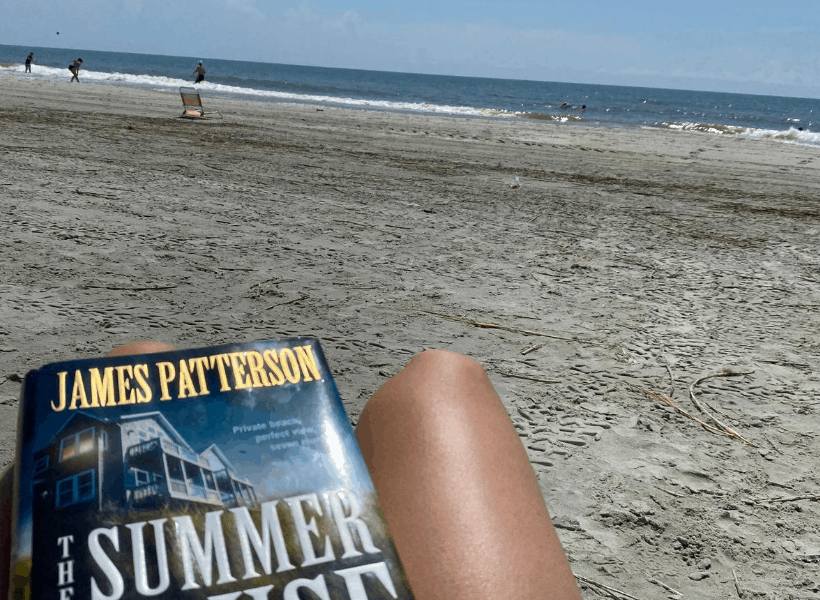 legs and book in picture with beach in background