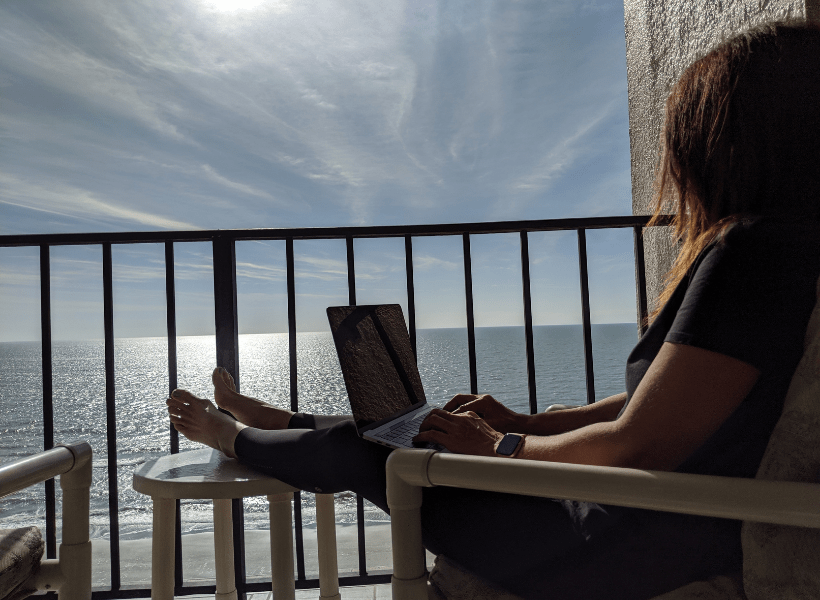 lady on laptop on balcony at the beach