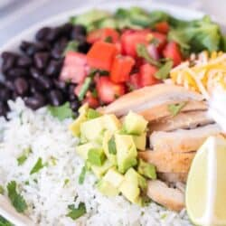 up close picture of rice bowl with burrito ingredients chicken sour cream, cheese, avocado, black beans, peppers and tomatoes