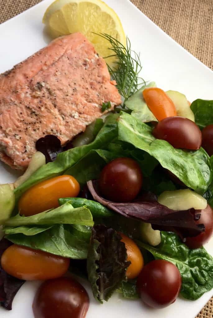 lemon dill salmon on a white plate with herbed salad and a lemon