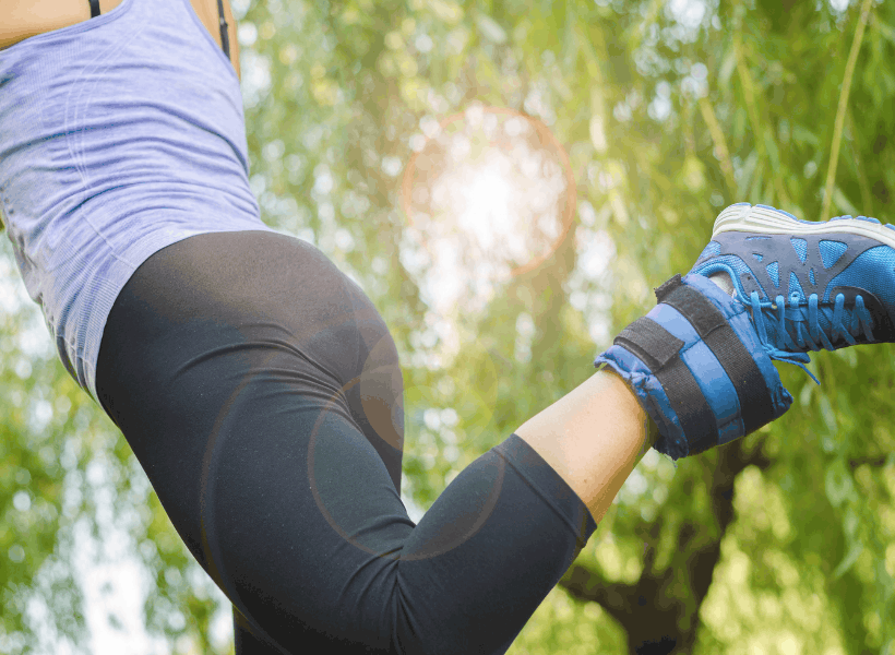 woman outside wearing black leggings, blue tennis shoes, lavender shirt exercising doing leg lifts with ankle weights