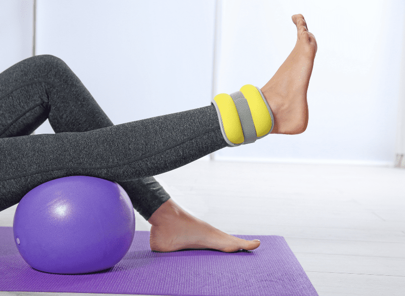 lady exercising on yoga ball lifting leg with ankle weight