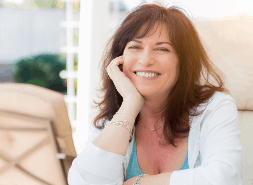 brunette woman with white sweater sitting with chin prompted up with arm and hand smiling at camera