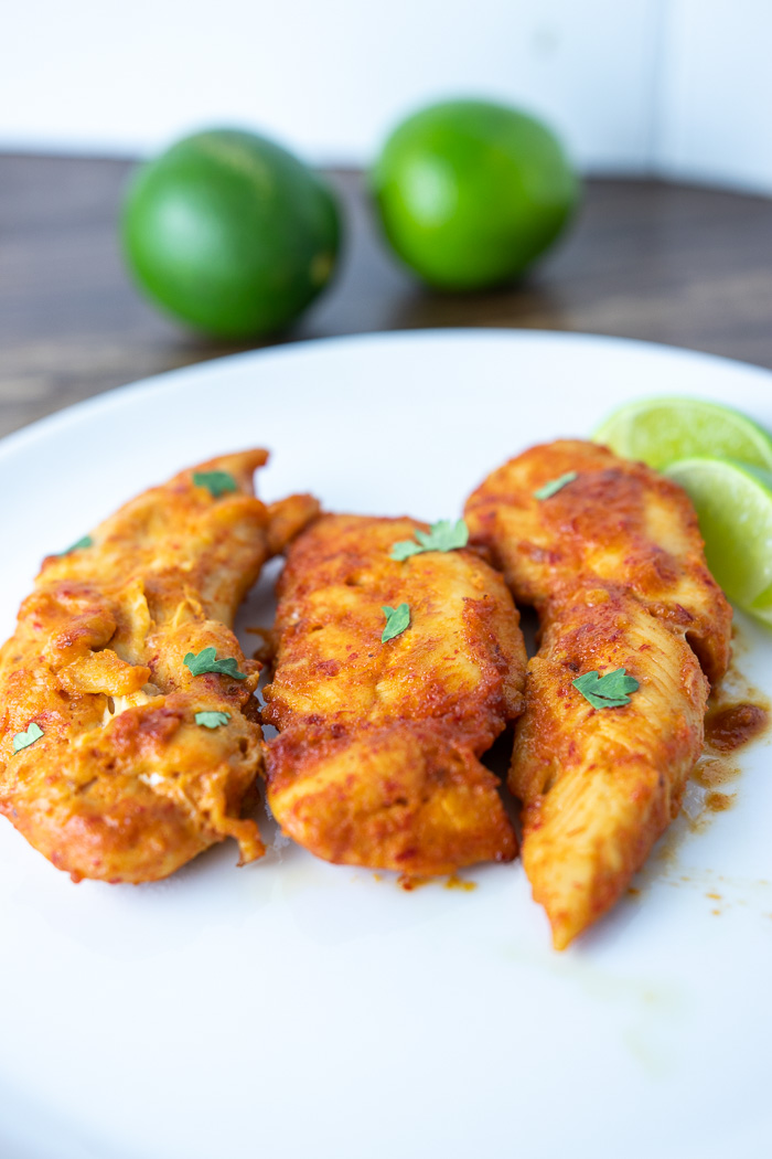 chipotle honey chicken tenders on a plate with limes