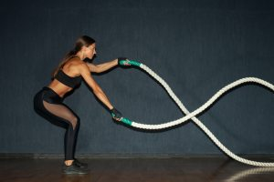 young hispanic athletic sportswoman with cross-fit rope