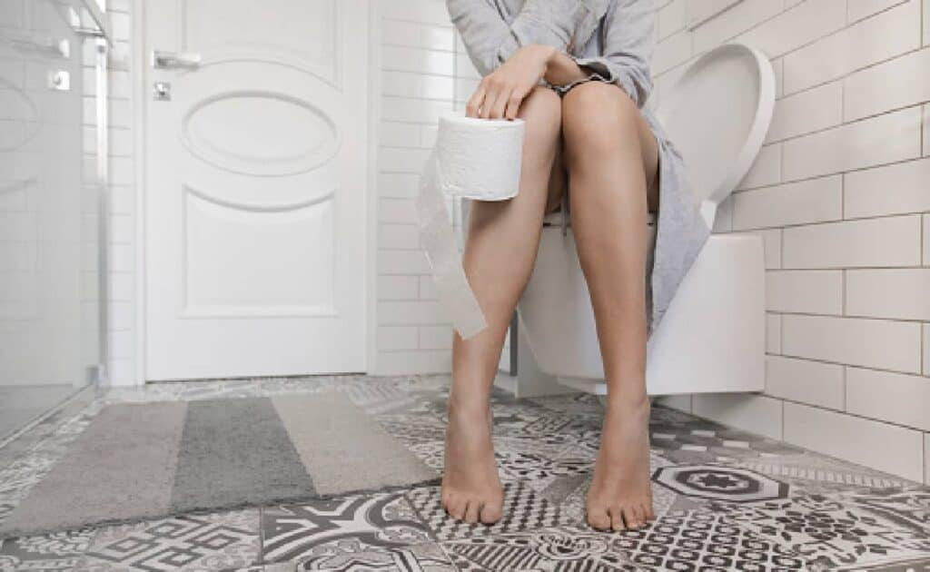 Woman sitting on the toilet holding toilet paper in her hand