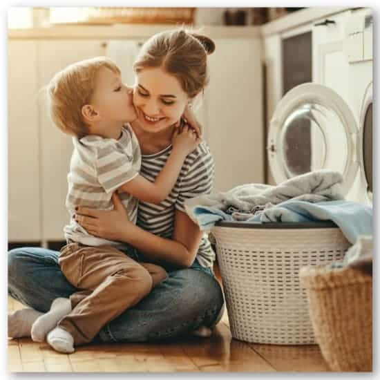 mom hugging son doing laundry