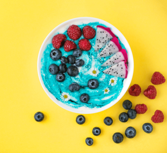 A bowl of berries on a colorful blue porridge.