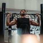A man in a black tanktop is doing seated shoulder press. He's no longer a beginner.