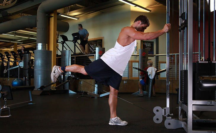 Man Working Out Cable Glute Kickback Machine