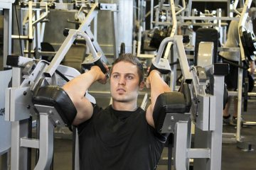 Man Working Out Using Tricep Extension Machine