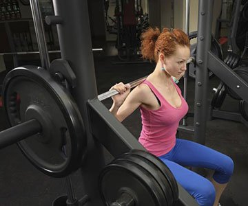 Woman Using Smith Machine Bar Weight For Fitness