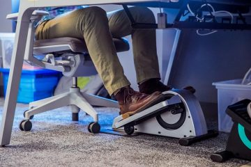 Man Using An Under Desk Elliptical For Health Fitness