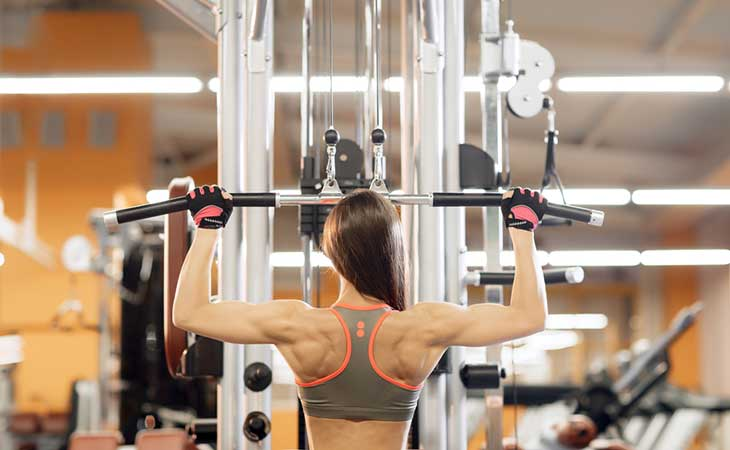 Woman Using A Standing Pulldown Machine