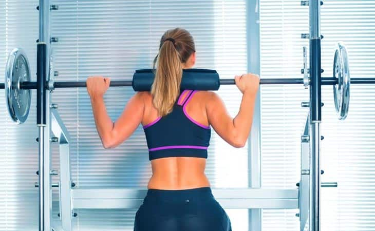 Woman Working Out Using Barbell Pad