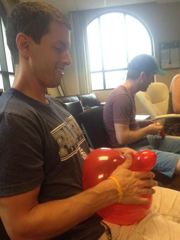 Mike attempting to push a ping pong ball through a balloon to simulate childbirth during our last Bradley Class