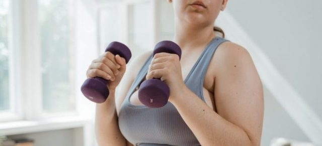 A girl working out with purple dumbells